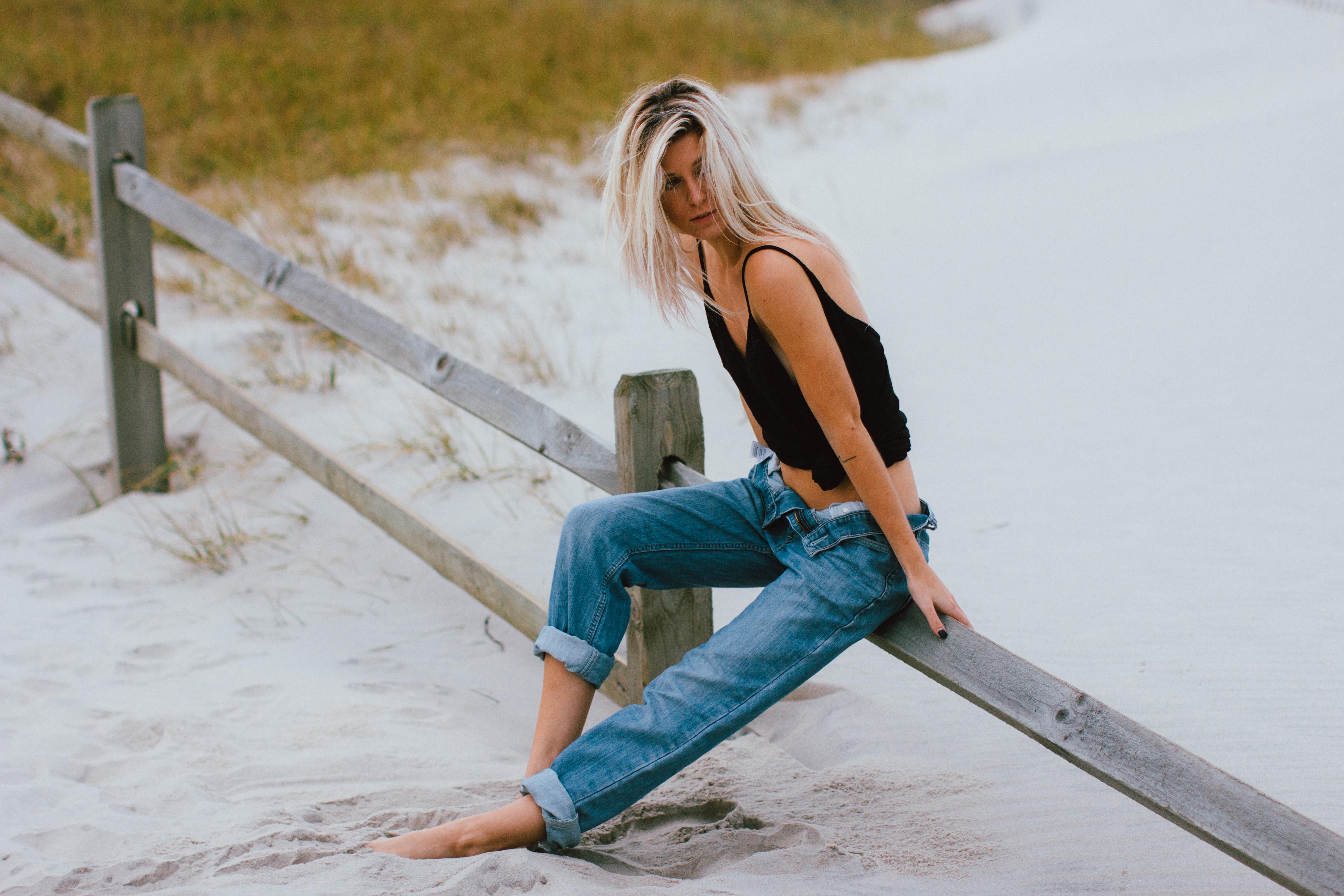 Девушка в джинсах сидящая на берегу моря